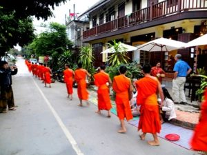 Monks in the early morning receiving alms from the locals. Luang Prabang.